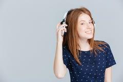 Música que escucha sonriente de la mujer en auriculares Imágenes de archivo libres de regalías