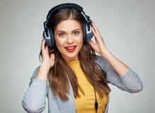 Música que escucha sonriente de la mujer feliz con los auriculares grandes Fotografía de archivo libre de regalías