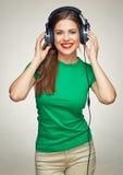Música que escucha sonriente de la mujer feliz con los auriculares grandes Fotografía de archivo