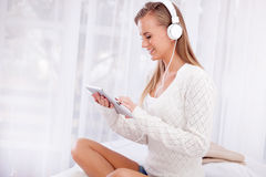 Música que escucha sonriente de la mujer joven con auriculares y usar un t Imagenes de archivo