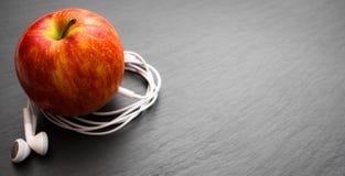 Música que juega la manzana en la cual los auriculares están conectados fotografía de archivo libre de regalías