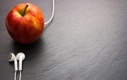 Música que juega la manzana en la cual los auriculares están conectados foto de archivo