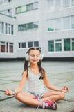 Música que se sienta y que escucha de la niña con los auriculares Fotografía de archivo libre de regalías
