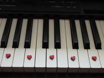 Música romántica, un pedazo de llaves del piano, blancas y negras con los pequeños corazones rojos foto de archivo libre de regalías