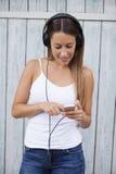 Música sem fio de escuta da mulher com fones de ouvido de um telefone esperto Fotografia de Stock