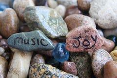Música y Joy Written en rocas del río Foto de archivo libre de regalías