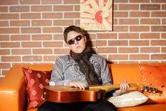 Músico adolescente joven que presenta con la guitarra Imágenes de archivo libres de regalías
