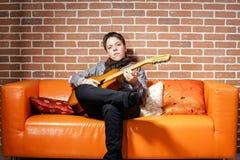 Músico adolescente joven que presenta con la guitarra Imagenes de archivo