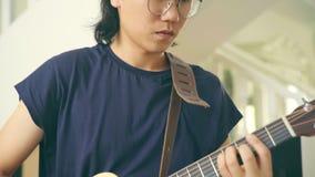 Músico asiático joven listo para tocar la guitarra almacen de metraje de vídeo
