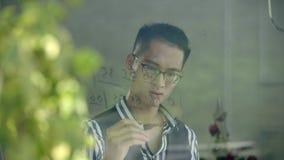 Músico asiático joven que escribe la notación musical numerada en el vidrio de la ventana almacen de video