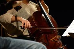 Músico clásico que toca el violoncelo durante funcionamiento Imagen de archivo