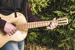 Músico com a guitarra na grama imagens de stock royalty free