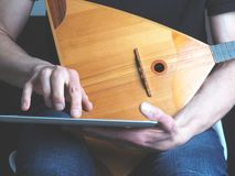 Músico com uma balalaica e um tablet pc foto de stock royalty free
