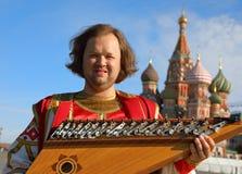 Músico con gusli ruso viejo del instrumento de música Fotos de archivo