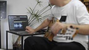 Músico con la guitarra eléctrica que trabaja en software en el estudio casero de la música almacen de metraje de vídeo