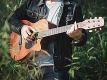 Músico considerável que joga a guitarra acústica no fundo do borrão do campo de grama Dia da música do mundo música e conceito do fotografia de stock