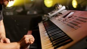 Músico considerável que joga teclados no concerto de rocha com o luminoso no clube noturno filme