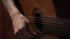Músico da guitarra que joga a música Equipe a mão que joga a música em uma guitarra acústica video estoque