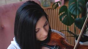 Músico da mulher na camisa branca que joga o violino filme