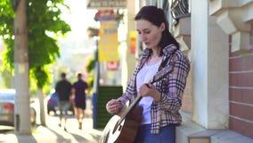 Músico da rua da menina, na camisa, jogando a guitarra mo lento vídeos de arquivo