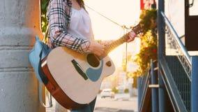 Músico da rua da menina, na camisa, jogando a guitarra mo lento irreconhecível filme