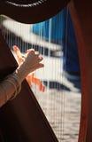 Músico da rua que joga a harpa nas ruas de Milão Fotos de Stock