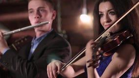 Músico de dos personas que juega música Una morenita hermosa en un vestido azul está jugando el violín, y al individuo en la chaq almacen de video
