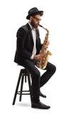 Músico de jazz que toca el saxofón y que se sienta en silla imagen de archivo