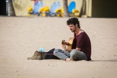 Músico de la calle con una guitarra que se sienta en la playa arenosa de la isla de Tenerife, España Foto de archivo libre de regalías