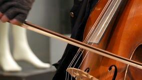 Músico de la calle que juega el cierre del violoncelo encima de la visión Violoncelista en de los guantes secuencias de arcos sua almacen de video