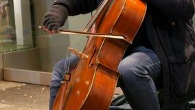 Músico de la calle que toca el violoncelo Violoncelista en de los guantes secuencias de arcos suavemente almacen de video