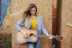 músico de la chica joven que toca la guitarra acústica Fotos de archivo libres de regalías