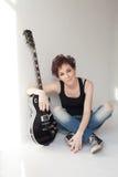 Músico de la muchacha con una guitarra que se sienta en el sitio blanco Imagen de archivo