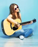 Músico de la muchacha que se sienta en un piso con la guitarra Fotos de archivo