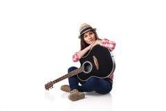 músico de la mujer con la guitarra que se sienta en piso Foto de archivo