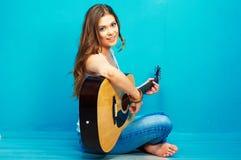 Músico de la mujer joven con la guitarra que se sienta en un piso Imagen de archivo libre de regalías