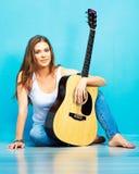Músico de la mujer joven con la guitarra que se sienta en un piso Imagen de archivo