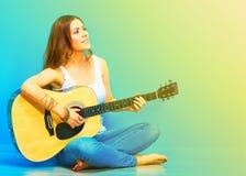 Músico de la mujer joven con la guitarra que se sienta en un piso Fotografía de archivo
