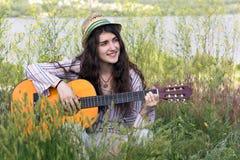 Músico de sexo femenino lindo que se sienta en hierba verde Fotografía de archivo