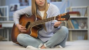 Músico de sexo femenino que adapta la guitarra en el sofá casero, disfrutando de la melodía, practicando metrajes