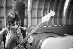 Músico de sexo femenino que toca la guitarra fuera de la estación de metro Fotos de archivo libres de regalías