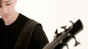 Músico de sexo masculino joven en ropa negra con una guitarra baja negra en un fondo blanco Música expresiva baja del guitarrista almacen de metraje de vídeo