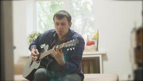 músico de sexo masculino que toca la guitarra acústica sirva jugar el vídeo de movimiento lento de la forma de vida de la guitarr almacen de metraje de vídeo
