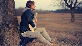 Músico de sexo masculino que toca la guitarra en la puesta del sol almacen de metraje de vídeo