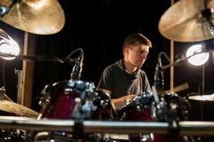 Músico de sexo masculino que toca los tambores y los platillos en el concierto Foto de archivo