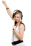 Músico del cantante de la muchacha con los auriculares que canta al micrófono Fotos de archivo libres de regalías