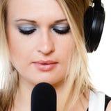 Músico del cantante de la muchacha con los auriculares que canta al micrófono Imágenes de archivo libres de regalías