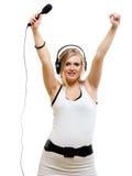 Músico del cantante de la muchacha con los auriculares que canta al micrófono Imagenes de archivo