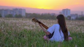 Músico del estallido de la niña que practica sus habilidades de la guitarra fuera de la ciudad toca la guitarra en parque actuaci metrajes
