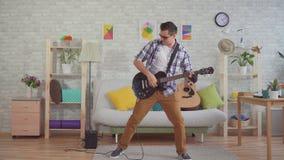 Músico del hombre joven con los vidrios que tocan emocionalmente la guitarra eléctrica metrajes